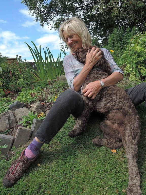 Barking Mad Dog Care Host Hugging Dog In Garden home boarding