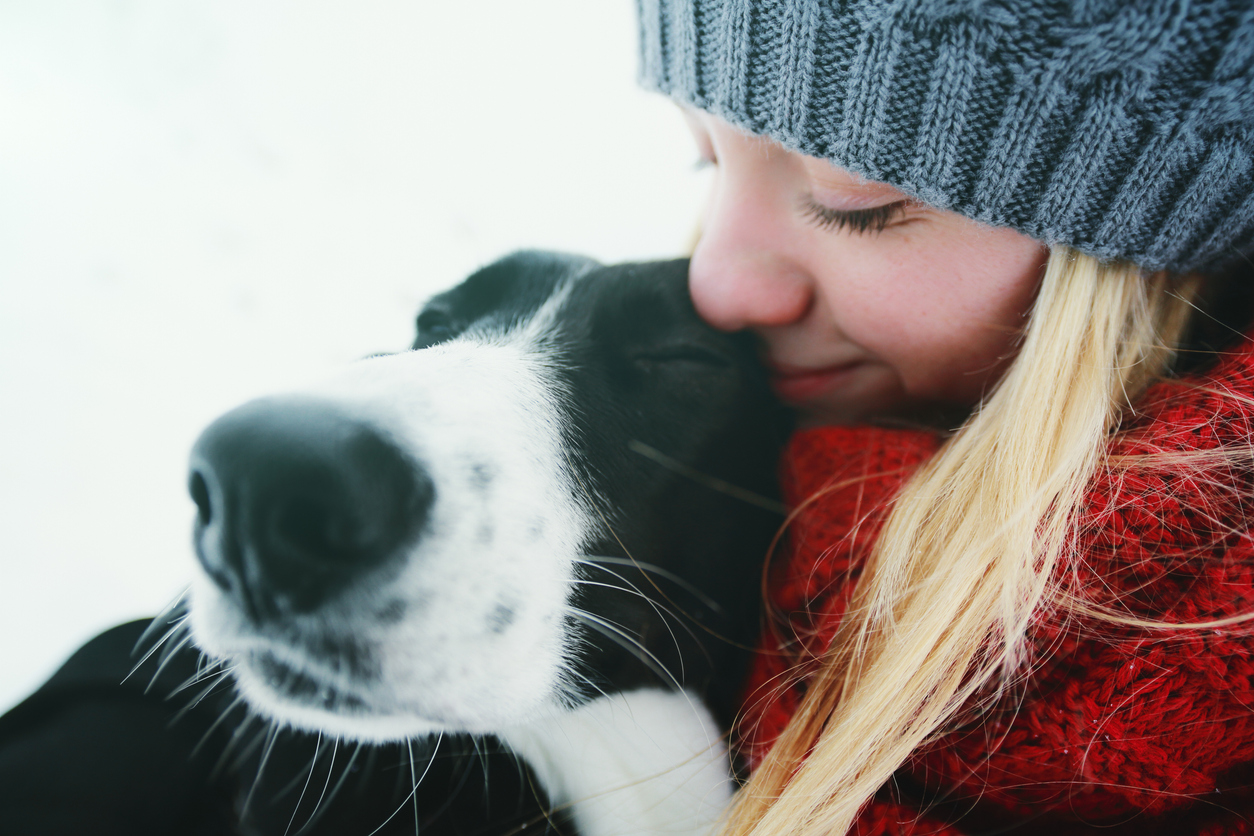Woman Hugging A Dog In A Winter Day